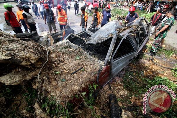 Petugas dibantu warga melakukan evakuasi mobil yang tertimpa pohon di