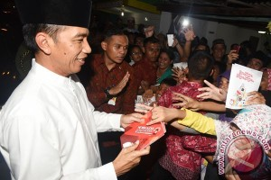 President Jokowi distributes health cards to plantation workers