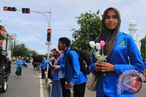 Murid membagikan bunga kepada guru saat Hardiknas