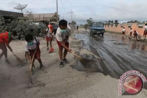 Siswa Bersihkan Jalan Tertutup Debu Vulkanik