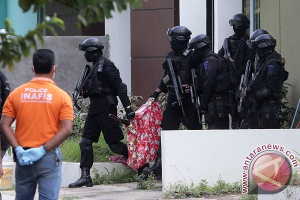 Anggota Tim Densus 88 Antiteror mengamankan sebuah tas yang berisi sebuah senjata laras panjang saat melakukan penggeledahan di salah satu rumah terduga teroris di Batam, Kepulauan Riau, Jumat (5/8/2016). (ANTARA FOTO/M N Kanwa)