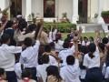Pelajar berebut menjawab pertanyaan Presiden Joko Widodo saat acara Gemar Baca dalam rangka Hari Buku Nasional di halaman tengah Istana Merdeka, Jakarta, Rabu (17/5/2017). Presiden dalam kesempatan tersebut berpesan agar pelajar bekerja keras dan rajin belajar untuk mengejar cita-cita. (ANTARA/Puspa Perwitasar)
