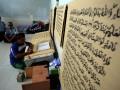 Kalapas Klas IIB Blitar Rudi Sardjono (tengah) memperhatikan seorang warga binaan saat menulis mushaf (lembaran) Alquran raksasa di Lapas Klas IIB Blitar, Jawa Timur, Selasa (13/6/2017). Kitab suci Alquran yang dikerjakan oleh seorang warga binaan bernama Ahmad Yani tersebut, memiliki ukuran halaman 90 x 120 centimeter dengan tulisan tangan dan ditargetkan rampung pada lima bulan mendatang. (ANTARA /Irfan Anshori)